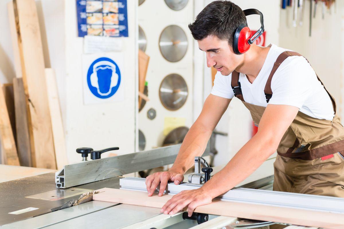 cabinet maker cutting wooden plank